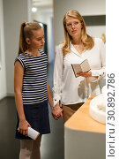 Купить «Young woman visitor with daughter with guide book looking at exhibition», фото № 30892786, снято 21 октября 2018 г. (c) Яков Филимонов / Фотобанк Лори