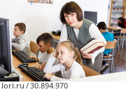 Купить «Female teacher working with schoolgirl in computer class», фото № 30894970, снято 19 декабря 2018 г. (c) Яков Филимонов / Фотобанк Лори