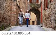 Купить «Women walk along a narrow street. Laugh and talk.», видеоролик № 30895534, снято 2 апреля 2020 г. (c) Константин Шишкин / Фотобанк Лори