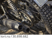 Купить «Detail of the chain transmission on the crown of an old vintage motorcycle with the mufflers on the side, the drum brake and the spoked wheel supported by the shock absorber.», фото № 30898682, снято 28 июля 2018 г. (c) easy Fotostock / Фотобанк Лори