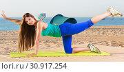 Купить «Woman in blue T-shirt is practicing stretching on the beach.», фото № 30917254, снято 4 августа 2017 г. (c) Яков Филимонов / Фотобанк Лори