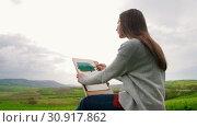 Купить «A young woman sits in the middle of a green field and draw. Hair blown in the wind», видеоролик № 30917862, снято 4 апреля 2020 г. (c) Константин Шишкин / Фотобанк Лори