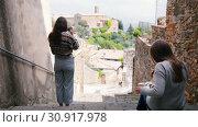 Купить «Two young women on the stairs. One of them draws, and the other photographs the landscape.», видеоролик № 30917978, снято 27 января 2020 г. (c) Константин Шишкин / Фотобанк Лори
