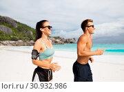 Купить «couple with phones and arm bands running on beach», фото № 30932986, снято 1 августа 2018 г. (c) Syda Productions / Фотобанк Лори