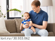 happy father with baby son sitting on sofa at home. Стоковое фото, фотограф Syda Productions / Фотобанк Лори