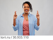 Купить «african american woman holding fingers crossed», фото № 30933110, снято 2 марта 2019 г. (c) Syda Productions / Фотобанк Лори