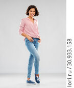 young woman in striped shirt, jeans and sneakers. Стоковое фото, фотограф Syda Productions / Фотобанк Лори