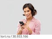 Купить «young woman in striped shirt using smartphone», фото № 30933166, снято 6 марта 2019 г. (c) Syda Productions / Фотобанк Лори