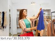 Купить «happy woman choosing clothes at clothing store», фото № 30933370, снято 19 февраля 2016 г. (c) Syda Productions / Фотобанк Лори