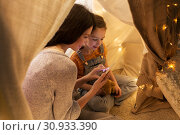 Купить «happy family with smartphone in kids tent at home», фото № 30933390, снято 27 января 2018 г. (c) Syda Productions / Фотобанк Лори