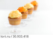 Купить «cupcakes with frosting on confectionery stands», фото № 30933418, снято 6 июля 2018 г. (c) Syda Productions / Фотобанк Лори
