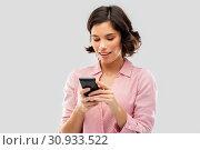 Купить «young woman in striped shirt using smartphone», фото № 30933522, снято 6 марта 2019 г. (c) Syda Productions / Фотобанк Лори
