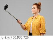 Купить «happy teenage girl taking picture by selfie stick», фото № 30933726, снято 28 февраля 2019 г. (c) Syda Productions / Фотобанк Лори