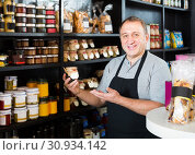 Купить «salesman working in delicatessen section of ordinary grocery», фото № 30934142, снято 5 октября 2016 г. (c) Яков Филимонов / Фотобанк Лори