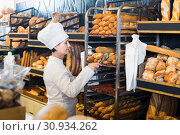 Купить «Middle aged female employee with tasty bread products», фото № 30934262, снято 4 октября 2016 г. (c) Яков Филимонов / Фотобанк Лори