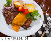 Well-done beef steak with baked potatoes and cheese served at plate. Стоковое фото, фотограф Яков Филимонов / Фотобанк Лори