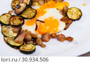 Купить «Plate with scrambled eggs with lard and zucchini at table on table», фото № 30934506, снято 18 июля 2019 г. (c) Яков Филимонов / Фотобанк Лори