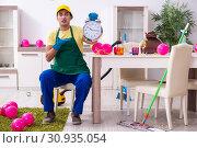 Купить «Young male contractor doing housework after party», фото № 30935054, снято 14 марта 2019 г. (c) Elnur / Фотобанк Лори