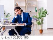 Купить «Young businessman sitting and working in the office», фото № 30935186, снято 18 марта 2019 г. (c) Elnur / Фотобанк Лори