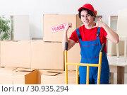 Купить «Young male contractor with boxes working indoors», фото № 30935294, снято 1 февраля 2019 г. (c) Elnur / Фотобанк Лори