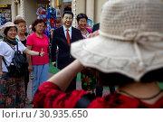 Купить «Китайские туристы фотографируются рядом со статуей лидера Китая Си Цзиньпиня на Арбате в центре города Москвы, Россия», фото № 30935650, снято 8 июня 2019 г. (c) Николай Винокуров / Фотобанк Лори