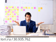 Купить «Young handsome employee in front of whiteboard with to-do list», фото № 30935762, снято 16 октября 2018 г. (c) Elnur / Фотобанк Лори
