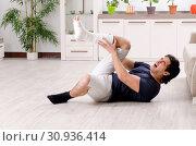 Купить «Leg injured young man suffering at home», фото № 30936414, снято 15 января 2019 г. (c) Elnur / Фотобанк Лори