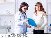 Купить «Young pregnant woman visiting experienced doctor gynecologist», фото № 30936442, снято 11 марта 2019 г. (c) Elnur / Фотобанк Лори