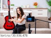 Купить «Female beautiful blogger playing guitar», фото № 30936478, снято 1 октября 2018 г. (c) Elnur / Фотобанк Лори