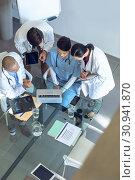 Купить «Medical team discussing over laptop at the table in hospital», фото № 30941870, снято 10 марта 2019 г. (c) Wavebreak Media / Фотобанк Лори