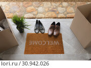 Купить «Footwear, cardboard boxes and plant near welcome doormat», фото № 30942026, снято 12 марта 2019 г. (c) Wavebreak Media / Фотобанк Лори