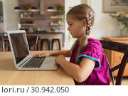 Купить «Cute girl using laptop on dining table in a comfortable home», фото № 30942050, снято 12 марта 2019 г. (c) Wavebreak Media / Фотобанк Лори