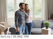 Купить «Happy beautiful couple looking away in new home», фото № 30942194, снято 12 марта 2019 г. (c) Wavebreak Media / Фотобанк Лори