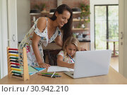 Купить «Mother helping her daughter with homework in a comfortable home», фото № 30942210, снято 12 марта 2019 г. (c) Wavebreak Media / Фотобанк Лори