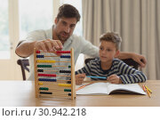 Father teaching his son mathematics with abacus in a comfortable home. Стоковое фото, агентство Wavebreak Media / Фотобанк Лори