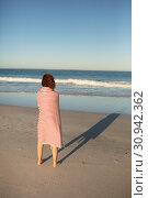 Купить «Woman wrapped in blanket standing on beach in the sunshine», фото № 30942362, снято 15 марта 2019 г. (c) Wavebreak Media / Фотобанк Лори