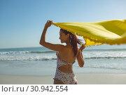 Купить «Woman in swimwear waving yellow scarf on the beach», фото № 30942554, снято 15 марта 2019 г. (c) Wavebreak Media / Фотобанк Лори
