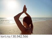 Купить «Woman performing yoga on the beach», фото № 30942566, снято 15 марта 2019 г. (c) Wavebreak Media / Фотобанк Лори
