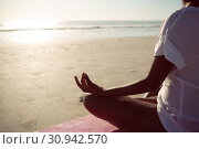 Купить «Woman performing yoga on the beach», фото № 30942570, снято 15 марта 2019 г. (c) Wavebreak Media / Фотобанк Лори