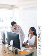 Купить «Female graphic designers talking with each other at desk in a modern office», фото № 30942870, снято 16 марта 2019 г. (c) Wavebreak Media / Фотобанк Лори