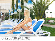 Купить «Young beautiful girl in a bathing suit resting on a lounger on a tropical resort with palm trees», фото № 30943702, снято 18 июля 2017 г. (c) katalinks / Фотобанк Лори