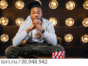 Black rapper in cap poses, perfomance on stage. Стоковое фото, фотограф Tryapitsyn Sergiy / Фотобанк Лори