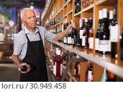 Купить «Elderly male vintner holding out bottle of wine», фото № 30949458, снято 8 мая 2019 г. (c) Яков Филимонов / Фотобанк Лори