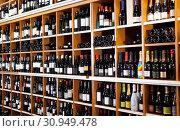 Купить «Rows of wine bottles on shelves in modern wine store waiting for customers», фото № 30949478, снято 8 мая 2019 г. (c) Яков Филимонов / Фотобанк Лори