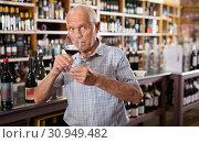 Купить «Confident elderly man tasting red wine in wine store before buying», фото № 30949482, снято 8 мая 2019 г. (c) Яков Филимонов / Фотобанк Лори