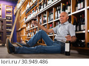 Купить «Glad man tasting red wine sitting on floor», фото № 30949486, снято 8 мая 2019 г. (c) Яков Филимонов / Фотобанк Лори