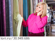 Купить «woman choosing curtains and using phone», фото № 30949686, снято 17 января 2018 г. (c) Яков Филимонов / Фотобанк Лори