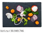 Купить «Vegetarian dish, carrots with greens, onion and tomatoe served at black plate», фото № 30949746, снято 20 июня 2019 г. (c) Яков Филимонов / Фотобанк Лори