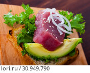 Купить «Tasty sandwich with raw tuna, avocado and greens at plate», фото № 30949790, снято 20 июня 2019 г. (c) Яков Филимонов / Фотобанк Лори