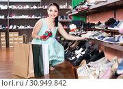 Купить «girl is choosing heeled sandals in shoes shop.», фото № 30949842, снято 10 мая 2017 г. (c) Яков Филимонов / Фотобанк Лори